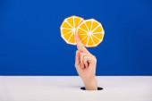 oříznutý pohled na ženu držící papír vystřižený oranžově izolovaný na modré