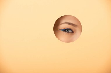 Cropped view of woman looking at camera through hole on orange stock vector