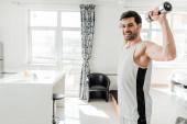 Boční pohled pohledný muž usmívá na kameru při tréninku s činkami doma