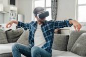 Usmívající se muž pomocí sluchátek virtuální reality na gauči