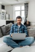 Freelancer poslech hudby ve sluchátkách a pomocí notebooku na gauči doma