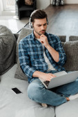 Fešák na volné noze ve sluchátkách pomocí notebooku v blízkosti smartphonu s prázdnou obrazovkou na gauči