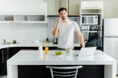 Férfi beszél okostelefon közelében laptop, gabonafélék és narancslé a konyhaasztalon