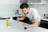 Hezký muž pomocí notebooku při snídani na stole v kuchyni