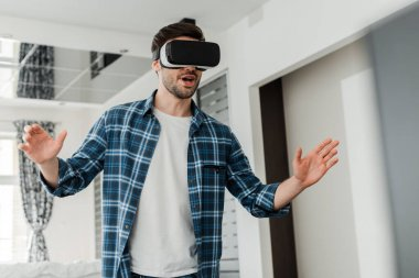 Excited man using virtual reality headset in living room stock vector