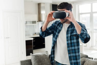 Man in plaid shirt using virtual reality headset at home stock vector
