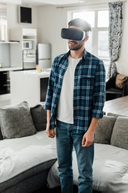 Man in checkered shirt using virtual reality headset near couch at home stock vector