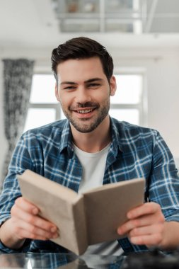 Selective focus of handsome man in plaited shirt smiling at camera while holding book at home stock vector