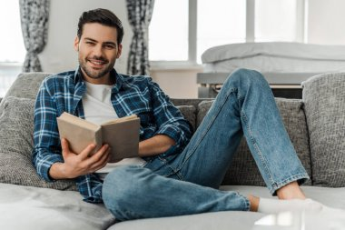 Selective focus of man smiling at camera while holding book on sofa at home stock vector