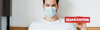 Man in medical mask holding card with quarantine lettering at home, panoramic crop stock vector