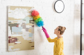 Photo Cute child in rubber gloves sweeping away dust from picture with feather duster in living room