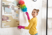 Photo Cute child in rubber gloves sweeping away dust from picture with feather duster, smiling and looking at camera in living room