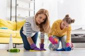 Matka a dcera se sprejem láhev a hadry otírání podlahy v blízkosti štětec v obývacím pokoji