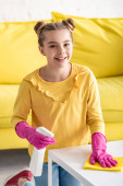 Nettes Kind lächelt, blickt in die Kamera, hält Sprühflasche in der Hand und wischt Couchtisch mit Lappen neben Sofa im Wohnzimmer