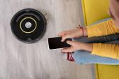 Ausgeschnittene Ansicht von Kind mit Smartphone auf Sofa in der Nähe von Staubsaugerroboter auf dem Boden im Wohnzimmer