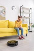 Nettes Kind mit Smartphone lächelt auf Sofa in der Nähe von Staubsaugerroboter auf dem Boden im Wohnzimmer