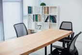 Photo Wooden table and chairs near rack with paper folders in office