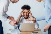 Válogatott fókusz az üzletemberek beszél a rémült afro-amerikai férfi közelében dokumentumok és kütyü az asztalon