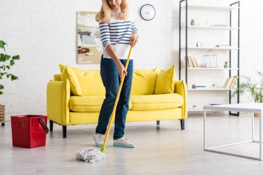 Cropped view of blonde woman cleaning up with mop in living room stock vector