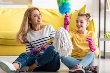 Mother and cute daughter with mop and feather duster smiling on floor in living room stock vector