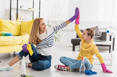 Mother and daughter with cleaning supplies giving high five, smiling and looking at each other on floor in living room stock vector