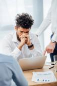 Válogatott fókusz az üzletember mutató laptop szomorú afro-amerikai kolléga az irodában