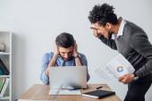 Africký americký podnikatel držící dokument a ukazující prstem na kolegu zakrývající uši v kanceláři