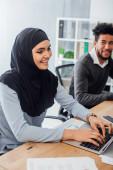 Selektivní zaměření usměvavé arabské podnikatelky pomocí notebooku poblíž afrického amerického kolegy v úřadu
