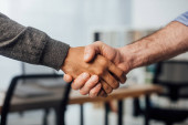 Oříznutý pohled na afrického amerického podnikatele potřásající si rukou s kolegou v úřadu