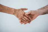 Photo Cropped view of men shaking hands isolated on grey