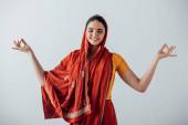Lächelndes indisches Mädchen meditiert isoliert auf grau