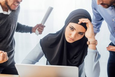 Selective focus of upset muslim businesswoman looking at camera near quarreling colleagues in office stock vector