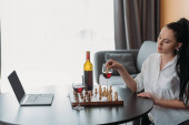 Photo attractive woman playing chess near laptop with blank screen and red wine on table