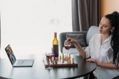 Photo young woman playing chess during video call with boyfriend near red wine on table