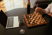 Photo cropped view of woman playing chess near laptop with blabk screen and red wine on table
