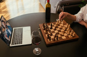 Photo cropped view of woman playing chess during video call with boyfriend near red wine on table