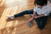 Photo overhead view of girl in medical mask looking at photo of boyfriend while sitting on floor