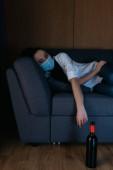 depressed woman in medical mask lying on sofa near bottle of wine on floor