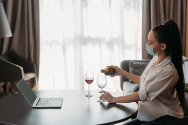 Side view of young woman in protective mask pouring wine into glass near laptop with blank screen stock vector