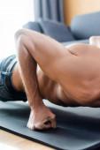 Oříznutý pohled na muže bez trička dělá press up na fitness podložku v obývacím pokoji