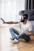 Muž používající virtuální realitu sluchátka při sezení na podlaze doma