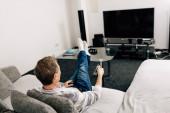 muž v džínách drží dálkový ovladač v blízkosti prázdné televizní obrazovky doma