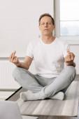 muž v ponožkách sedí v lotosové póze a ukazuje prostřední prsty