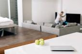 Fotografie selektiver Fokus von schmackhaften Äpfeln auf einem Tisch in der Nähe des Mannes, der sein Wohnzimmer reinigt