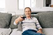 selektivní zaměření veselého muže držícího dálkové ovládání doma