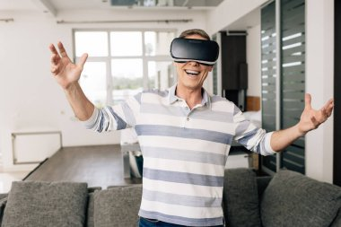 Happy man in virtual reality headset with outstretched hands at home stock vector