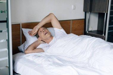 Sick man lying on bed and feeling unwell stock vector