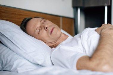 Selective focus of man sleeping in bedroom stock vector