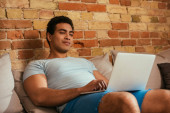 young bi-racial man chilling with laptop on sofa during self isolation