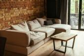 moderní interiér obývacího pokoje s béžovou pohovkou, stolem a dálkovým ovladačem